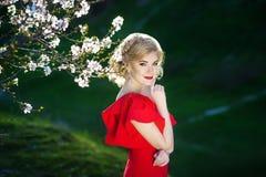 享用气味的美丽的愉快的少妇在一个开花的春天庭院里 免版税图库摄影
