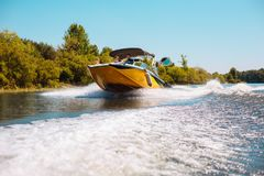 享用汽艇乘驾下来河的宜人的年轻家庭 免版税图库摄影