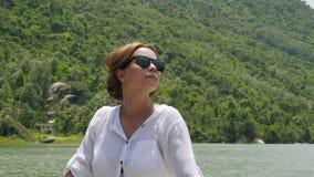 享用河和山的愉快的妇女盖了绿色放松在湖岸和看在天空的森林美丽的女孩 股票视频