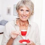 享用浓咖啡的一个资深夫人的画象 免版税图库摄影