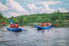 享用浪端的白色泡沫划皮船在河、极端和乐趣体育的年轻人在旅游景点 r 免版税库存照片