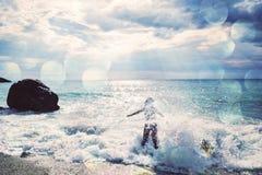 享用海波浪的美丽的妇女 查出的背面图白色 免版税库存照片