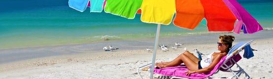 享用海滩的可爱的妇女 免版税库存图片