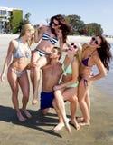 享用海滩的四个美丽的少妇 免版税库存照片