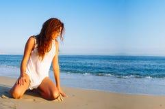 享用海滩的秀丽少妇在日落 库存图片