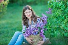 享用淡紫色庭院,有花的少妇的美丽的妇女在绿色公园 撕毁丁香的女孩在庭院里 库存照片