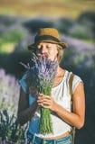 享用淡紫色的花束女孩佩带的草帽开花 免版税图库摄影
