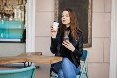 享用温暖和刷新的咖啡的女孩在午餐期间 坐在咖啡馆,饮用的茶的繁忙和成功的妇女 免版税库存图片