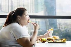 享用炸薯条的肥胖妇女在餐馆 库存照片