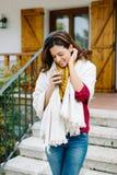 享用热的咖啡杯外面秋天的轻松的妇女 免版税库存照片
