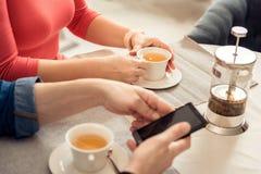 享用热的饮料的男人和妇女在自助食堂 免版税库存图片