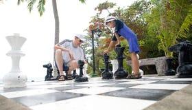 享用父亲比赛与实物大小一样的儿子的棋 免版税库存图片