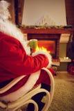 享用的圣诞老人喝茶为圣诞节假日 免版税库存图片