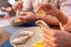 享用的端庄的妇女吃地中海食物 免版税库存照片