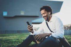 享用的耳机的年轻非裔美国人的人坐在晴朗的城市公园和听到在他巧妙的电话的音乐 库存照片