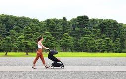 享用皇家宫殿的庭院的一个年轻母亲在有她的放松在他的婴儿车的小婴孩的东京 免版税图库摄影
