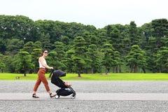 享用皇家宫殿的庭院的一个年轻母亲在有她的放松在他的婴儿车的小婴孩的东京 免版税库存照片