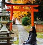 享用秋天在日本寺庙,京都的女孩槭树叶子 免版税库存照片
