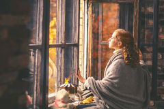 享用秋天空气的愉快的妇女在开窗口 库存图片
