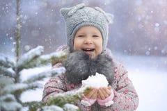 享用第一雪的小女孩 免版税库存图片