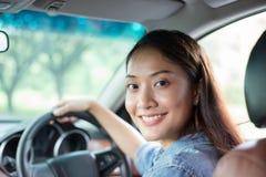享用美丽的亚裔的妇女微笑和 驾驶在路的一辆汽车 免版税图库摄影