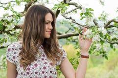 享用自然和开花的花的美丽的微笑的妇女 免版税图库摄影