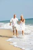 享用节假日前辈星期日的海滩夫妇 免版税库存照片