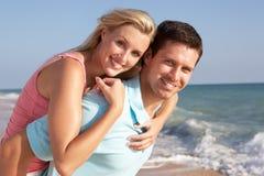 享用节假日星期日年轻人的海滩夫妇 免版税库存照片
