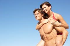 享用节假日肩扛年轻人的海滩夫妇 库存图片
