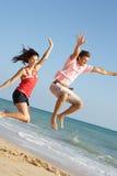 享用节假日跳的年轻人的海滩夫妇 库存图片