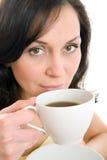 享用茶妇女年轻人的杯子 免版税库存照片