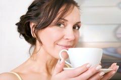 享用茶妇女的杯子 库存照片