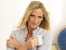 享用茶的白肤金发的杯子 免版税库存照片
