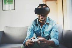享用虚拟现实玻璃的可爱的非洲人,当坐沙发时 有vr耳机或3d的愉快的年轻人 免版税图库摄影