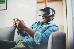 享用虚拟现实玻璃的微笑的非洲人,当坐沙发时 有vr耳机或3d的愉快的年轻人 库存照片
