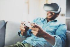 享用虚拟现实玻璃的微笑的非洲人,当坐沙发时 有vr耳机或3d眼镜的年轻人 免版税库存照片