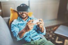 享用虚拟现实玻璃的微笑的非洲人,当放松在沙发时 有vr耳机或3d眼镜的年轻人 免版税图库摄影