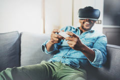享用虚拟现实玻璃的愉快的非洲人,当坐沙发时 有vr耳机或3d眼镜的年轻人和 免版税库存照片