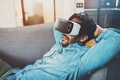 享用虚拟现实玻璃的有胡子的非洲人,当在家时放松在沙发 被弄脏的背景,火光 免版税库存照片