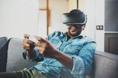 享用虚拟现实玻璃的有胡子的非洲人,当坐沙发时 有vr耳机或3d的愉快的年轻人 库存照片