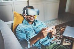 享用虚拟现实玻璃的有胡子的非洲人,当放松在沙发时 有vr耳机或3d的愉快的年轻人 库存图片