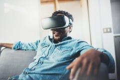 享用虚拟现实玻璃耳机或3d眼镜的微笑的有胡子的非洲人,当放松在沙发在现代时 图库摄影