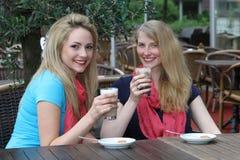 享用被冰的咖啡的女性朋友 免版税图库摄影