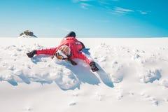 享用雪的女子滑雪者晒日光浴和微笑 免版税库存图片