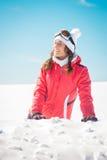 享用雪的少妇滑雪者微笑和晒日光浴 免版税图库摄影