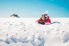 享用雪的少妇滑雪者晒日光浴 免版税库存照片