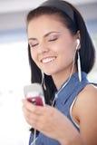 享用音乐微笑的妇女年轻人 免版税库存图片