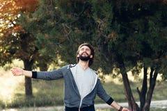 享用风的微笑的人吹在森林里 免版税库存图片