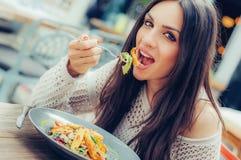 享用食物的少妇在餐馆,有她的午餐brea 库存照片