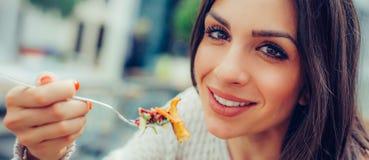 享用食物的少妇在餐馆,有她的午餐brea 免版税库存图片